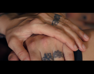 Hands with tattooed wedding bands